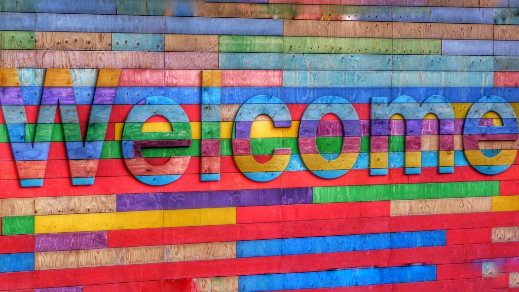 "Sign made of multicoloured wooden panelsreading ""Welcome""."