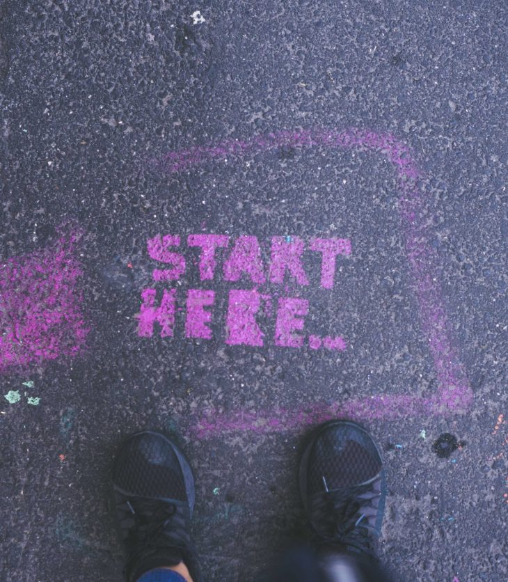 'Start here' in pink text painted on road