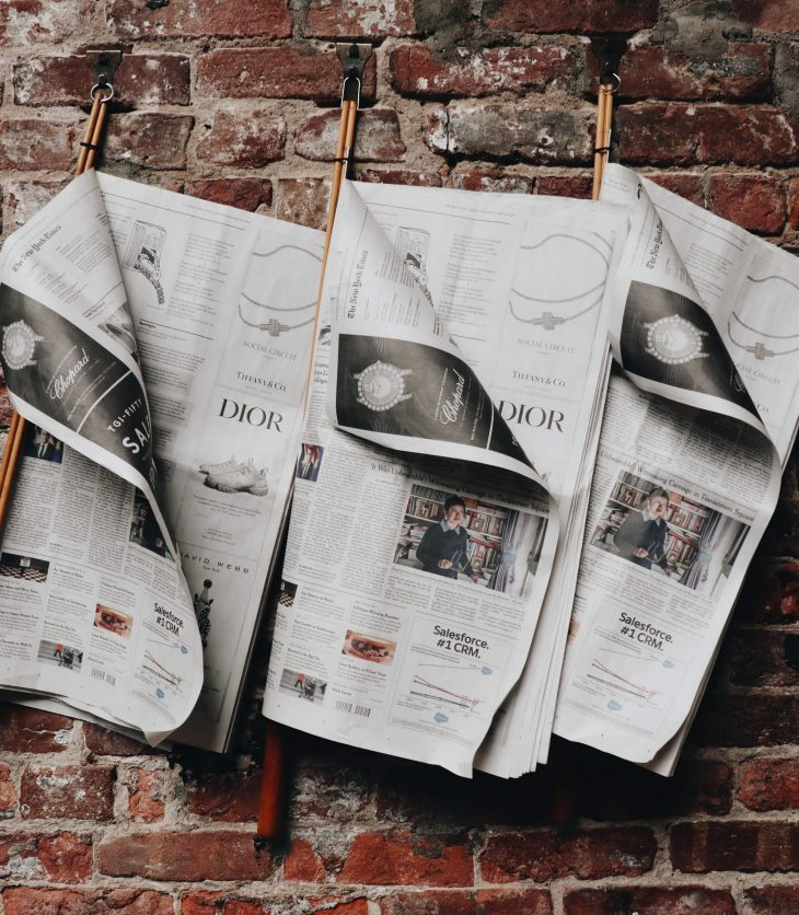 Newspapers hanging from brickwall