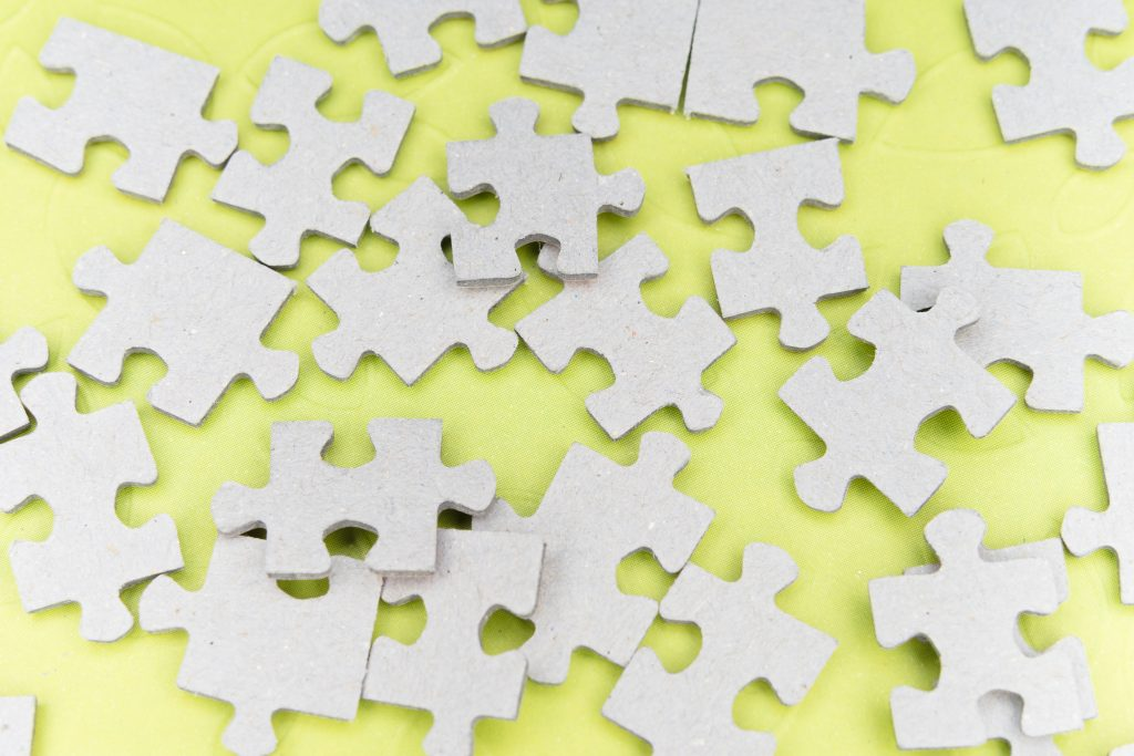 Blank cardboard puzzle pieces on a lemon yellow background
