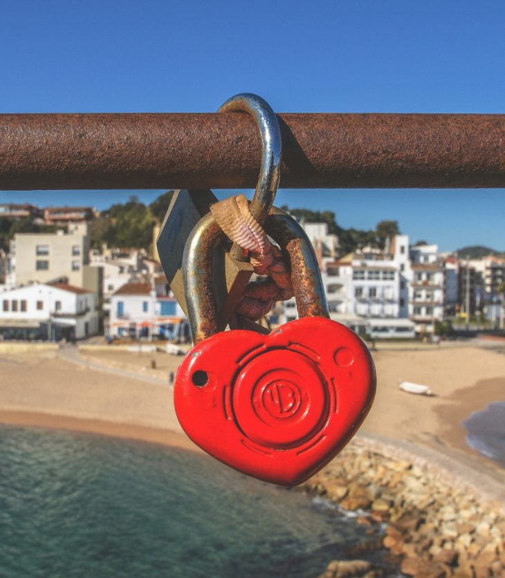 Red heart shaped padlock on a rusted metal bar. A beach is in the background.