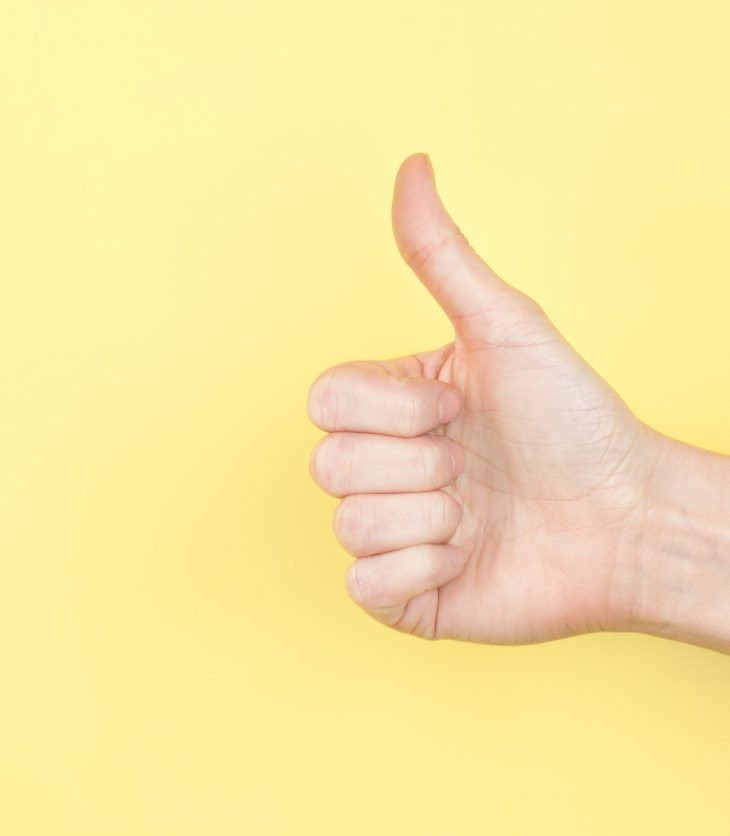Thumbs up on yellow backdrop