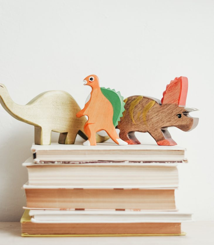three wooden dinosaurs on top of book stack