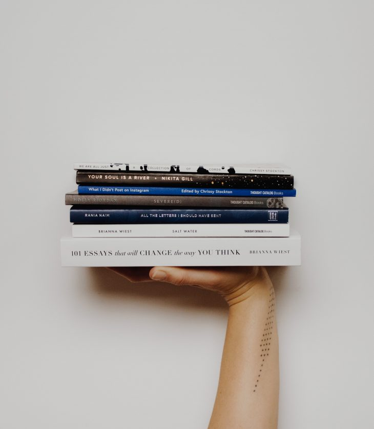 persons arm holding pile of books