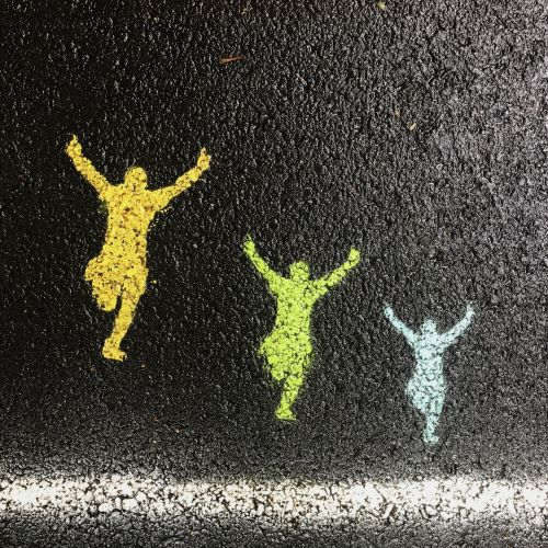 Start line on tar road with spray painted figures jumping in the air